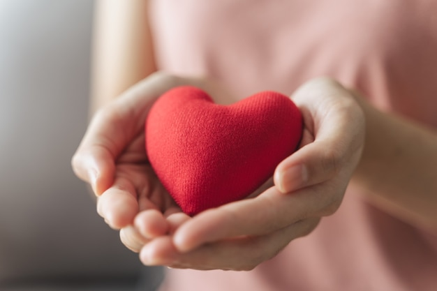 Mulher segura coração vermelho amor seguro saúde doação feliz caridade voluntária dia saúde mental