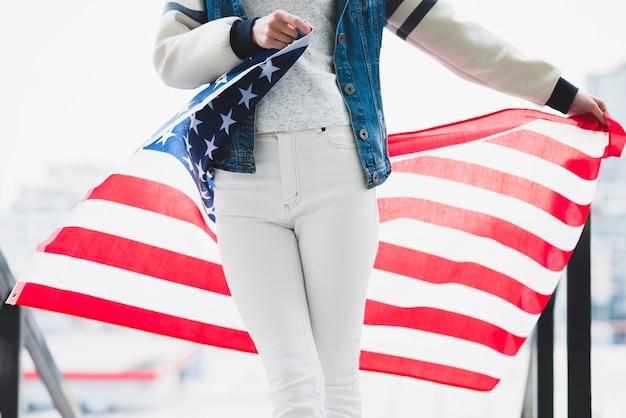 Mulher segura, desdobrado, bandeira americana, atrás de, pernas
