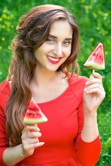 Mulher segura dois pedaços de melancia
