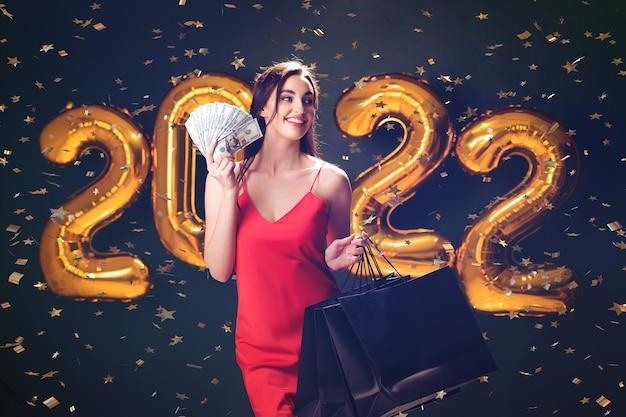 Mulher segura dólares e compra compras de ano novo, vendas de balões pretos na sexta-feira, comemora