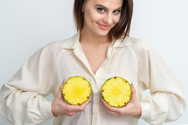 Mulher segura duas metades de abacaxi. conceito de glândulas mamárias saudáveis e beleza da pele.