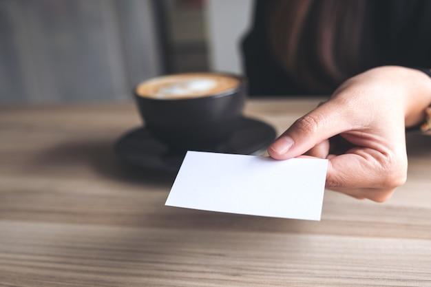 Mulher segura, e, dar, um, vazio, cartão negócio, para, alguém, com, xícara café, ligado, tabela