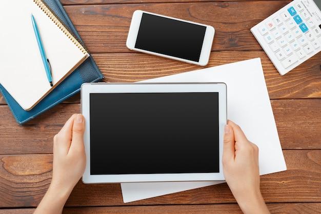 Mulher segura, em branco, tabuleta, dispositivo, sobre, um, madeira, workspace, tabela