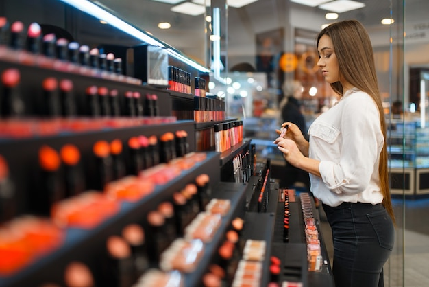 Mulher segura esmalte na prateleira da loja de cosméticos. comprador em vitrine em salão de beleza de luxo, cliente mulher no mercado de moda