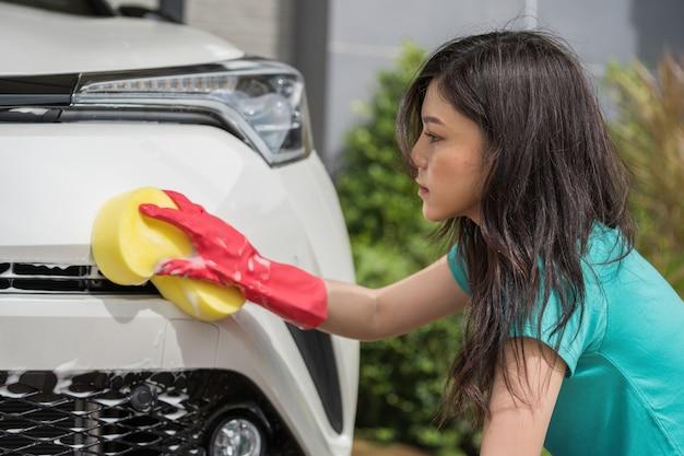 Mulher segura, esponja, para, lavando carro