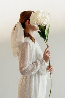 Mulher segura, flor, vista lateral