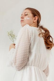 Mulher segura, flores, vista baixa ângulo