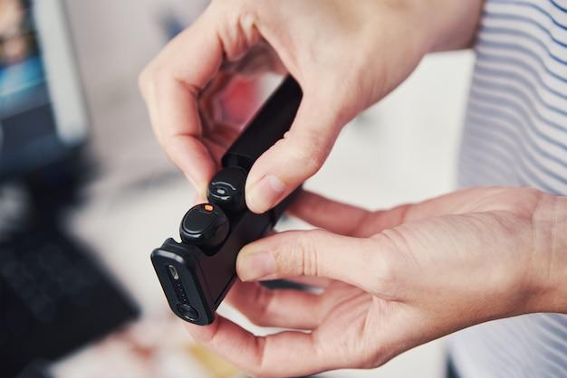 Mulher segura fones de ouvido sem fio. usando fones de ouvido para ouvir música