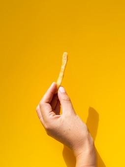 Mulher segura, frita, frente, fundo amarelo