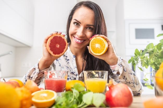 Mulher segura laranja cortada vermelha e amarela nas mãos com sucos frescos na frente dela.