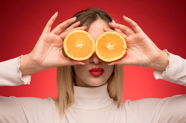 Mulher segura, laranja, fatias, sobre, dela, olhos