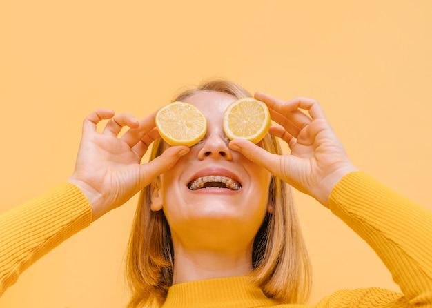 Mulher segura, limões, frente, olhos, em, um, amarela, cena