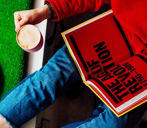 Mulher segura, livro, e, xícara café