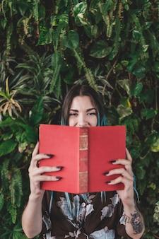 Mulher segura, livro, frente, dela, boca, ficar, contra, planta