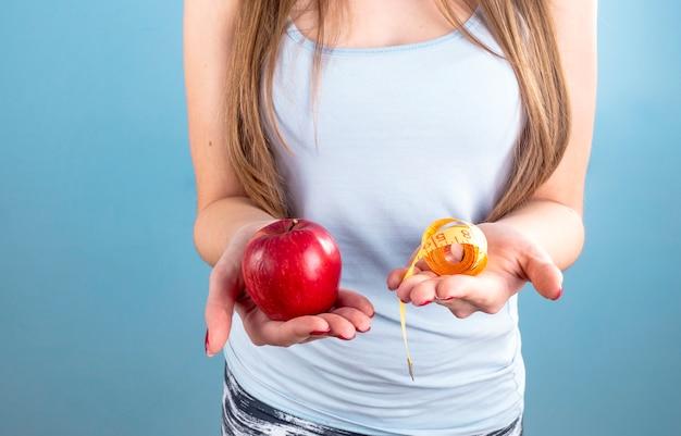 Mulher segura, maçã vermelha, com, medindo fita, em, mãos