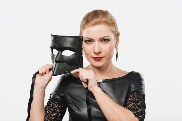 Mulher segura, máscara preta, em, mãos