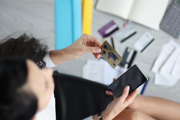 Mulher segura na mão um cartão de cartão de crédito de plástico e pagamento por smartphone para serviços via aplicativo móvel