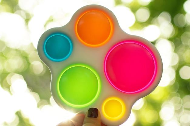 Mulher segura na mão um novo brinquedo sensorial de plástico e silicone - covinha simples.