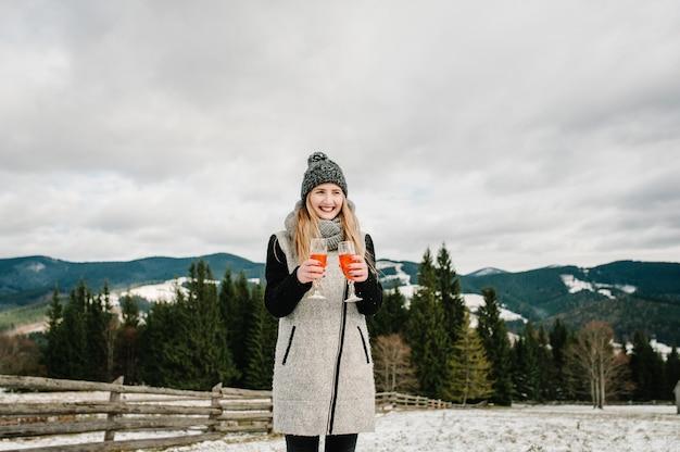 Mulher segura nas mãos uma duas taças com champanhe no fundo das montanhas de inverno.