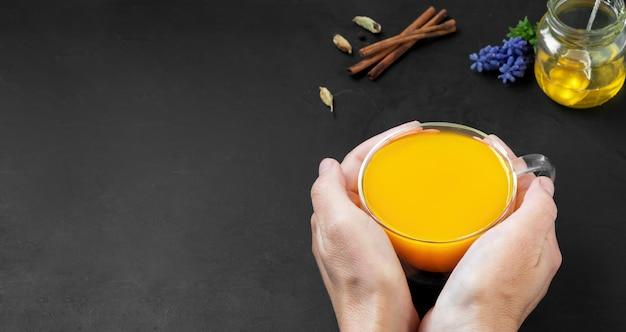 Mulher segura nas mãos uma xícara de bebida natural e saudável feita de açafrão e especiarias