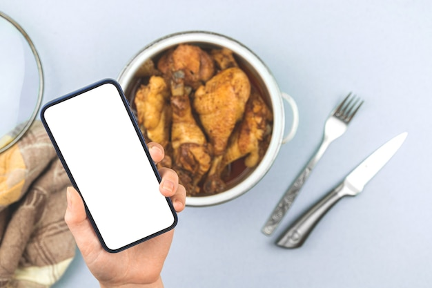 Mulher segura o celular com tela de maquete com frango assado em casa, frango frito em uma panela, menu de comida saudável para foto do conceito de restaurante, tela branca, foto do espaço de cópia