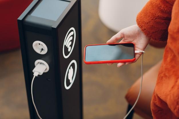 Mulher segura o celular na mão em stand para carregamento e wi-fi