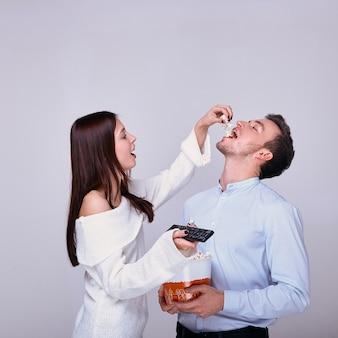Mulher segura o controle remoto da tv e derrama pipoca na boca do cara