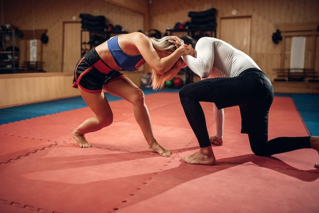 Mulher segura o controle, treino de defesa pessoal com personal trainer masculino