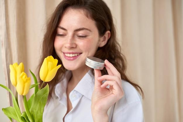 Mulher segura o frasco com produto de beleza na mão com tulipas amarelas e fundo de cortina bege