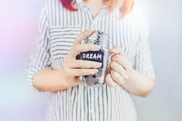 Mulher segura o frasco de vidro de moedas para a garrafa dos seus sonhos com economia financeira para entretenimento e lei ...