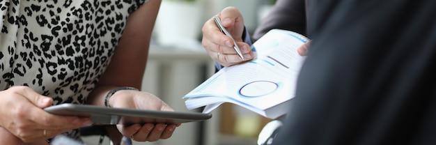 Mulher segura o tablet nas mãos ao lado dos homens com uma caneta esferográfica e documentos nas mãos no escritório closeup. conceito de assinatura de contratos de negócios.