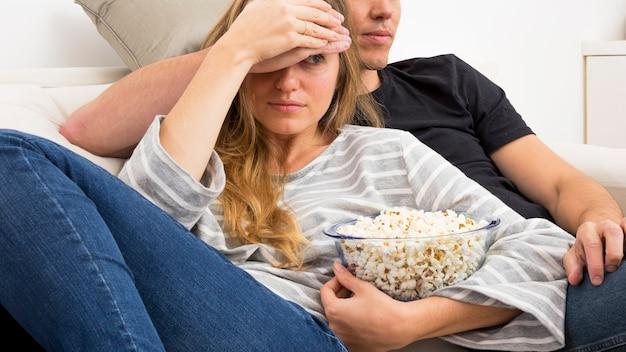Mulher segura, pipoca, espreitar, enquanto, olhando televisão, casa