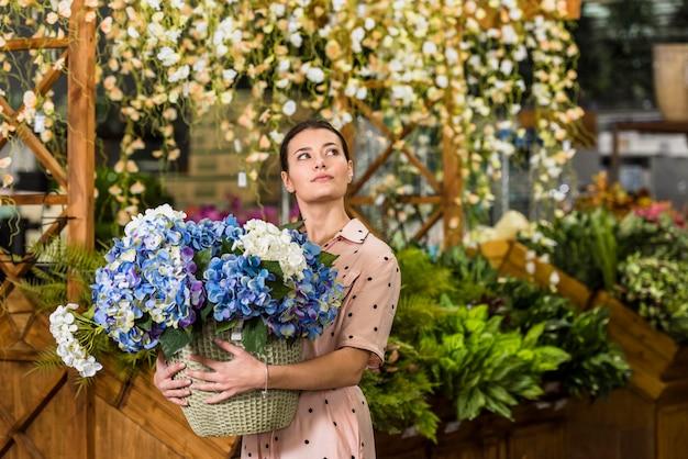 Mulher segura, pote, com, flores, em, casa verde