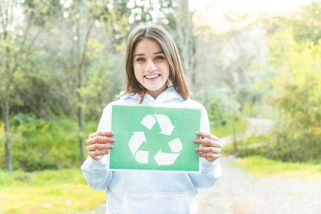 Mulher segura, recicle símbolo, em, floresta