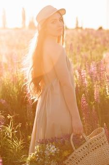 Mulher segura, saco vime, em, dela, mãos, desgastar, chapéu fedora, ligado, pôr do sol, em, lupine, campo