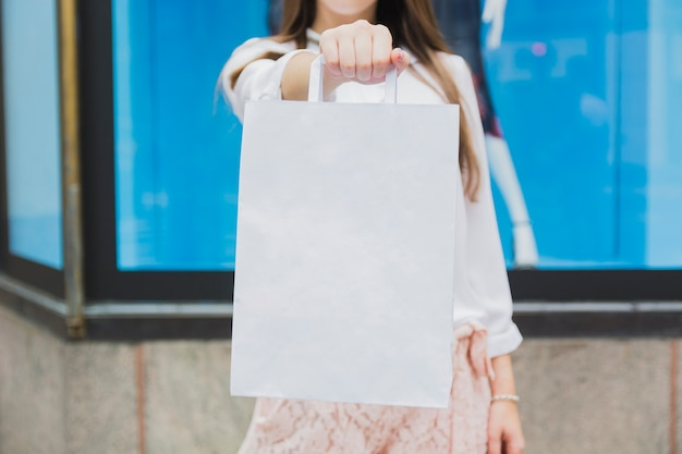 Mulher segura, sacola compras, perto, vitrina