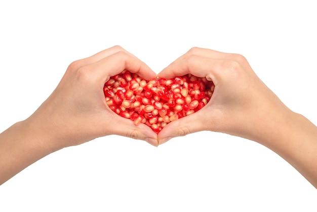 Mulher segura sementes de romã. símbolo do coração, isolado no branco.