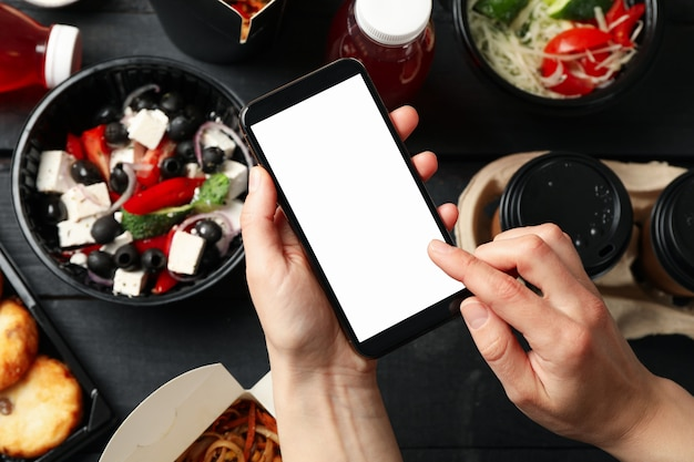 Mulher segura smartphone. comida em caixas para levar com fundo de madeira