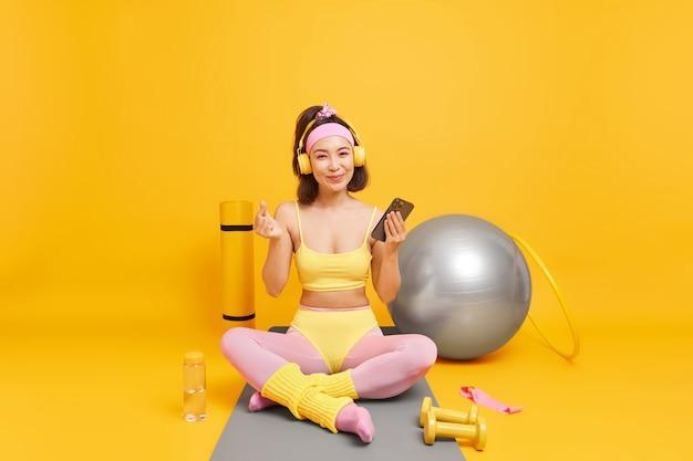 Mulher segura smartphone verifica resultados de treinamento físico, faz coreano como se estivesse de bom humor faz poses de ioga em karemat confortável
