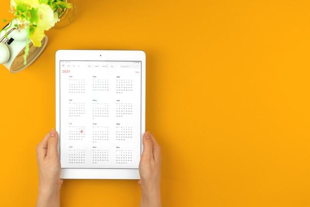 Mulher segura tablet com calendário 2021, plano de fundo de conceito de organizador de eventos e planejamento com foto do espaço de cópia
