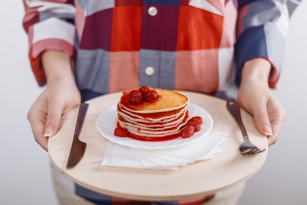 Mulher segura, tábua cortante, com, prato, panquecas americanas, com, geleia de framboesa