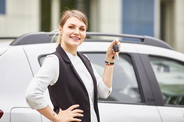 Mulher segura, teclas, para, carro novo automático, e, sorrindo