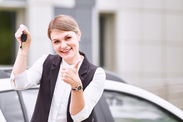 Mulher segura, teclas, para, novo, carro automóvel, e, sorrindo, câmera