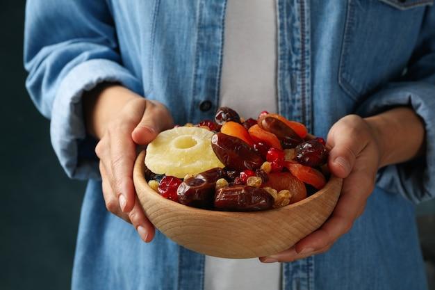 Mulher segura tigela com frutas secas, close-up