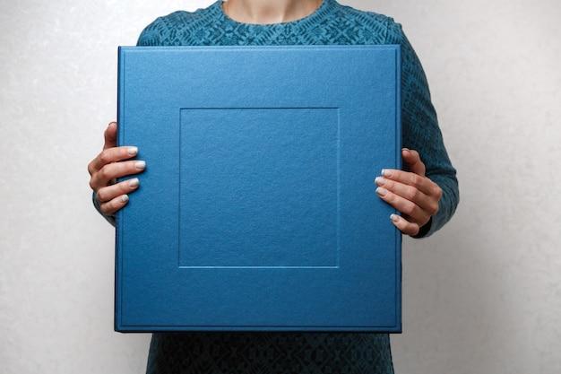 Mulher segura um álbum de família em elegante caixa quadrada designer. femininas mãos segurando uma caixa quadrada foto para álbum de casamento. grande caixa de presente azul nas mãos de mulher fechar com espaço de cópia de texto