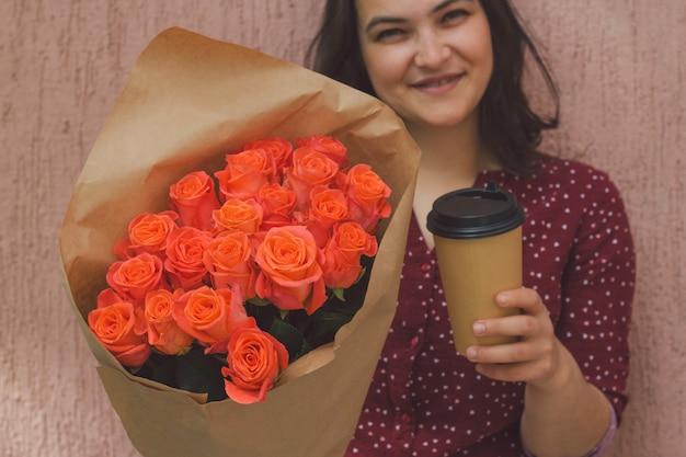 Mulher segura, um, buquê rosas, e, um copo papel, de, levar, bebida