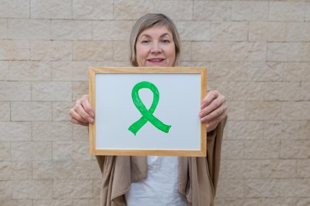 Mulher segura um cartaz com uma fita verde para conscientizar e apoiar as pessoas que convivem com a doença.