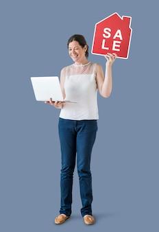 Mulher segura, um, casa, venda, ícone, e, um, laptop