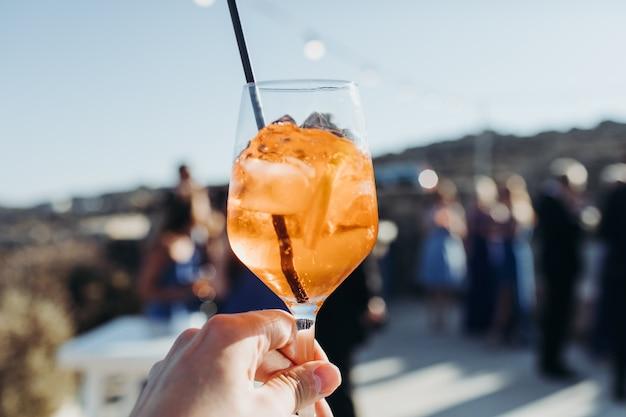 Mulher segura um copo com bebida de laranja com cubos de gelo contra o sol