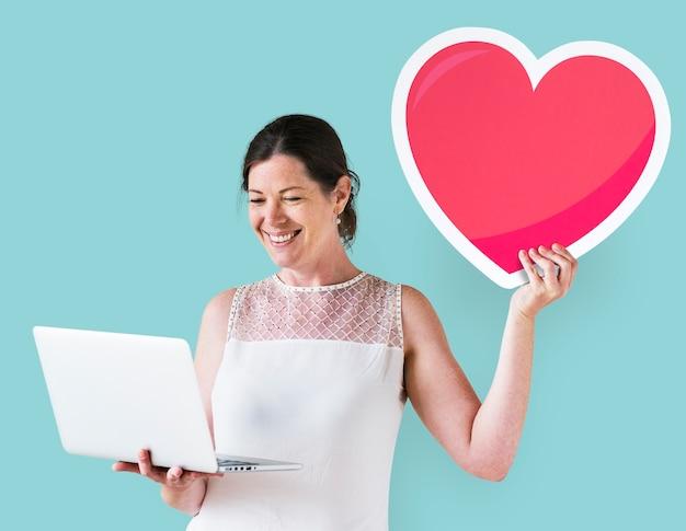 Mulher segura, um, coração, emoticon, e, um, laptop